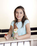 Smiling Girl Holding Chocolate Ice Cream Cone At Counter. Portrait of smiling girl holding chocolate ice cream cone at counter in parlor Stock Image