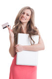 Smiling girl holding closed laptop and a credit card Stock Images