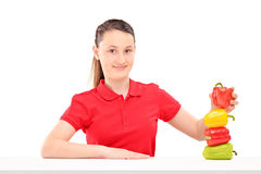 A smiling girl holding colorful peppers on a table Stock Images