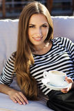 Smiling girl is holding cup of hot coffee Royalty Free Stock Photo