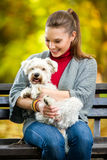 Smiling girl  holding cute maltese dog. In park Royalty Free Stock Photography