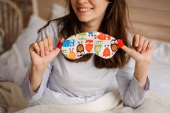 Smiling girl holding a cute sleep mask with the owl print. Young smiling girl holding a cute sleep mask with the owl print on the background of a white bed stock photos