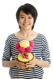 Smiling girl holding flower. Smiling asian young girl holding congratulation toy flower, isolated Royalty Free Stock Images
