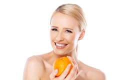 Smiling girl is holding fresh orange Royalty Free Stock Images