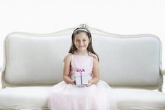 Smiling Girl Holding Gift On Sofa Stock Image