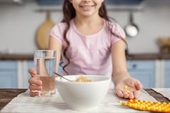 Smiling girl holding a glass of water and vitamins. Healthy lifestyle. Little smiling dark-haired girl holding a glass of water and little yellow sweet vitamins Royalty Free Stock Photo