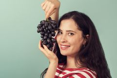 Smiling girl holding grapes near her face and smiling broadly to the viewer. Stock Image