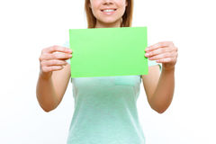 Smiling girl holding green sheet of paper stock photo