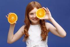 Smiling girl holding halves of orange Royalty Free Stock Photography