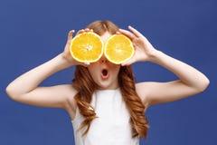 Smiling girl holding halves of orange Stock Image