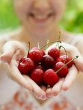 Smiling girl holding a handful of  cherries. Smiling girl holding a handful of red cherries Royalty Free Stock Images