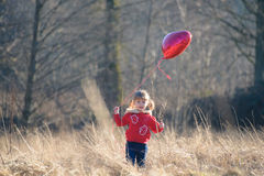 Smiling girl holding heart-shaped balloon Stock Photo