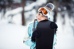 Smiling girl holding her snowboard Royalty Free Stock Image
