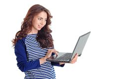 Smiling girl holding laptop. Lets chat. Nice pretty young girl holding laptop and looking at it while having pleasant conversation online Stock Images