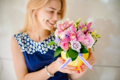Smiling girl holding a little bouquet of flowers. Smiling girl holding a little bouquet of beautiful and colorful flowers in hands no face close up Royalty Free Stock Image