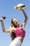 Smiling girl holding maracas and hat in air Stock Photos