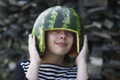 Smiling girl holding melon hemlet on her head Royalty Free Stock Images
