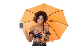 Smiling girl holding a mobile phone under an umbrella Royalty Free Stock Photo