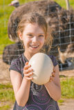 Smiling girl holding ostrich egg Stock Photos