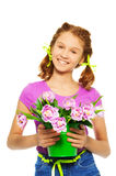 Smiling girl holding pail with pink tulips. On the white background stock images