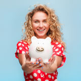 Smiling girl holding piggy toy. Curly haired blonde smiling girl wearing red shirt whit white dots holding porcelain pig looking at camera Royalty Free Stock Photos