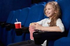 Free Smiling Girl Holding Popcorn Bucket, Sitting In Cinema. Stock Photo - 143078550