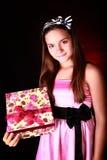 Smiling girl holding present over dark Stock Photos