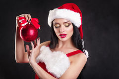 Smiling girl holding a red  Christmas tree balls. Women on dress and santa`s hat. Santa`s helper .Attractive happy girl in santa h Royalty Free Stock Image