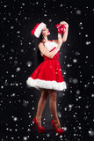 Smiling girl holding a red  Christmas tree balls. Women on dress and santa`s hat. Santa`s helper .Attractive happy girl in santa h Stock Image