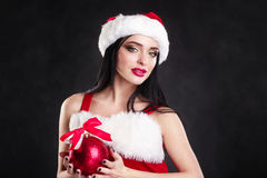 Smiling girl holding a red  Christmas tree balls. Women on dress and santa`s hat. Santa`s helper .Attractive happy girl in santa h Royalty Free Stock Photography