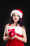 Smiling girl holding a red  Christmas tree balls. Women on dress and santa`s hat. Santa`s helper .Attractive happy girl in santa h Stock Photos