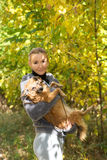 Smiling girl holding a red dog in autumn Park Royalty Free Stock Images