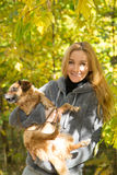 Smiling girl holding a red dog in autumn Park Stock Photography