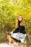 Smiling girl holding a red dog in autumn Park Royalty Free Stock Photography