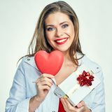 Smiling girl holding red heart with gift box. Stock Photos