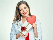Smiling girl holding red heart with gift box. Royalty Free Stock Photo