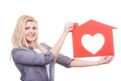 Smiling girl holding red paper house with heart shape Royalty Free Stock Image