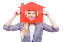 Smiling girl holding red paper house with heart shape Stock Photos