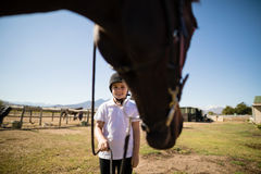 Smiling girl holding the rein of the horse in the ranch Royalty Free Stock Photography