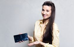 Smiling girl holding smarthpone with dirty touch screen. Smiling girl holding smarthpone with dirty touch screen royalty free stock image