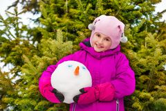 Smiling girl holding snowman's head in forest Royalty Free Stock Photos