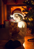 Smiling girl holding sparkling present under Christmas tree Stock Photography