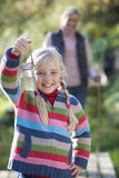 Smiling girl holding specimen jar outdoors Stock Photo