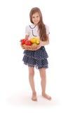 Smiling girl holding straw basket with fruits Stock Image