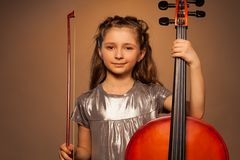 Smiling girl holding string to play violoncello Royalty Free Stock Photography