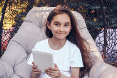 Smiling  girl holding  tablet PC, sitting in a park at summer da Royalty Free Stock Photography
