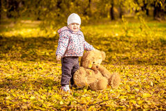 Smiling girl holding teddy bear at autumn park Royalty Free Stock Photo