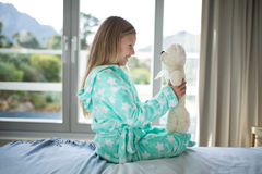 Smiling girl holding teddy bear on bed in bedroom Stock Photo