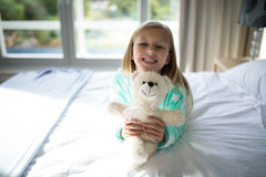 Smiling girl holding teddy bear on bed in bedroom Royalty Free Stock Photos