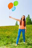 Smiling girl holding three balloons in summer Royalty Free Stock Photos